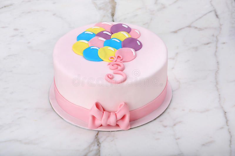 Birthday cake with balloons on a stone background royalty free stock photos