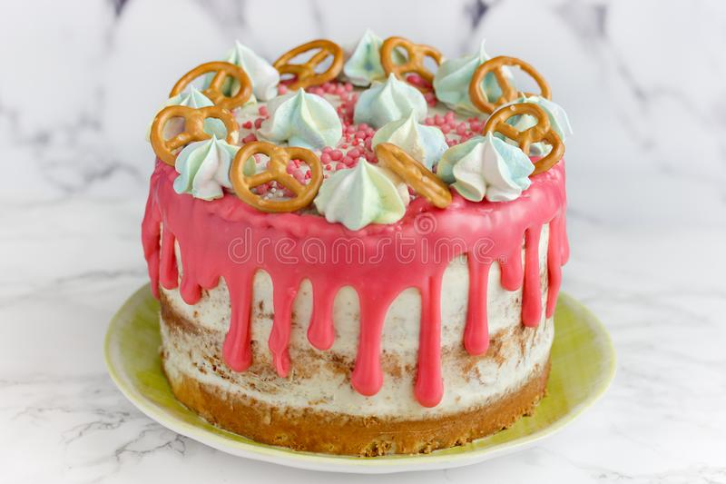 Birthday cake. Decorated with pink icing, meringue, sprinkle and cookies stock photo