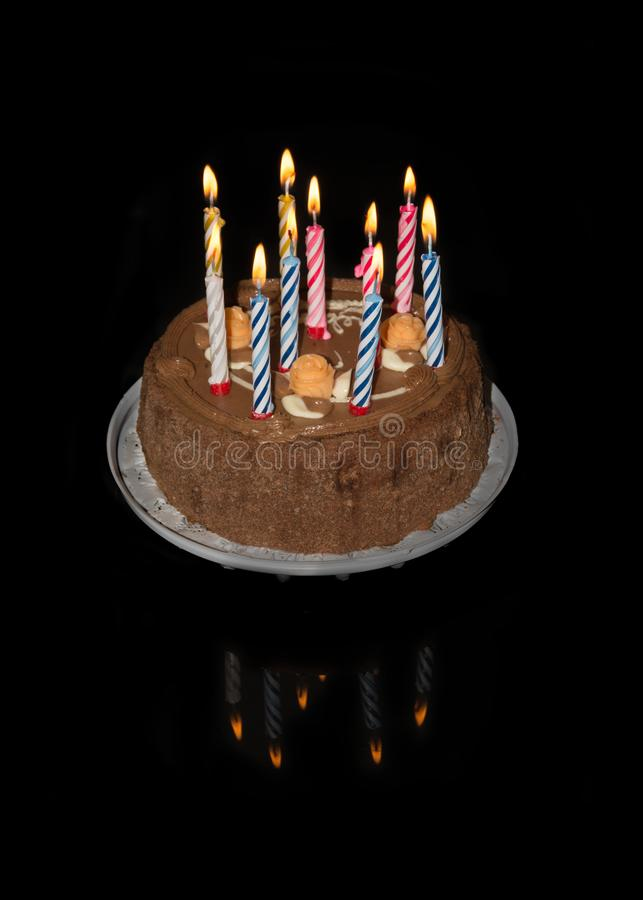 Birthday cake on black background with ten colorful lit candles stock images