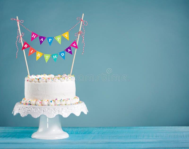 Birthday Cake with bunting. White Buttercream birthday cake with colorful bunting and sprinkles over blue background stock photos