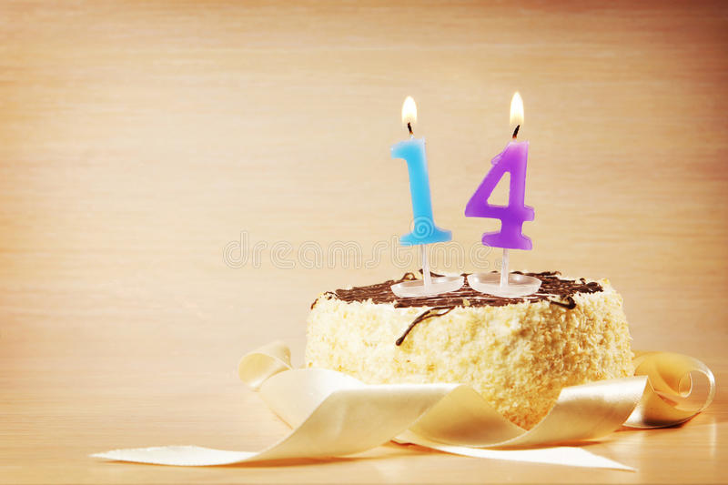 Birthday cake with burning candle as a number fourteen. Focus on the candle stock photo
