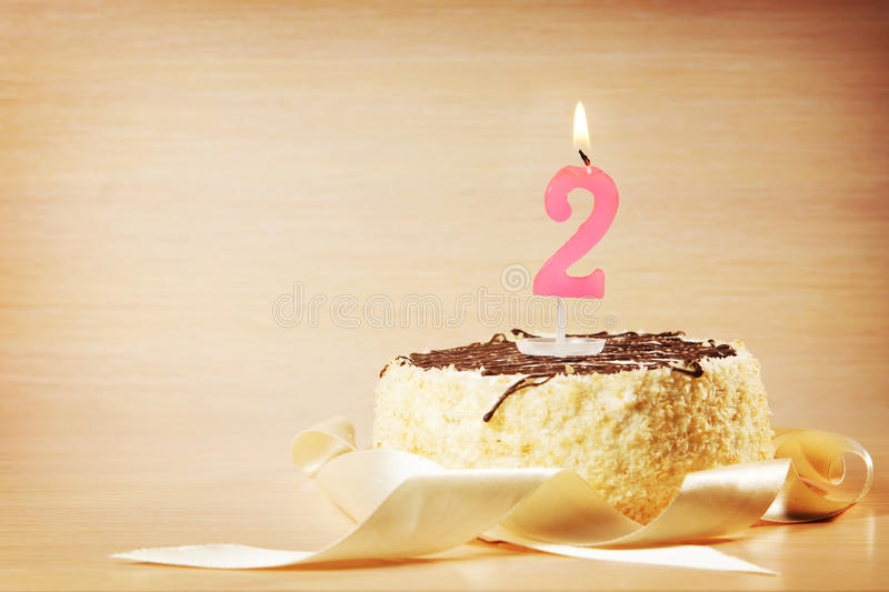 Birthday cake with burning candle as a number two. Focus on the candle stock photos