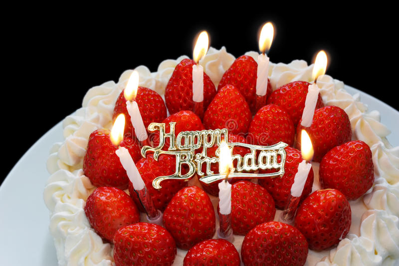 Birthday cake with burning candles. Birthday cake with burning candle on black background stock photography