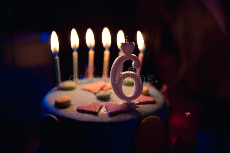 Birthday cake with burning candles and age 6 candle in the dark background with candies in decor. Birthday multicolored cake with burning candles and age 6 stock image
