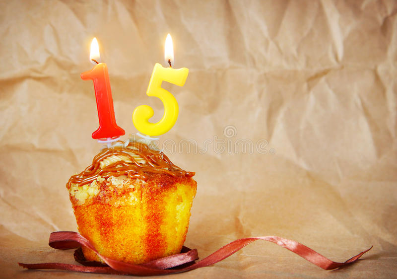 Birthday cake with burning candles as number fifteen. On brown paper background royalty free stock photos