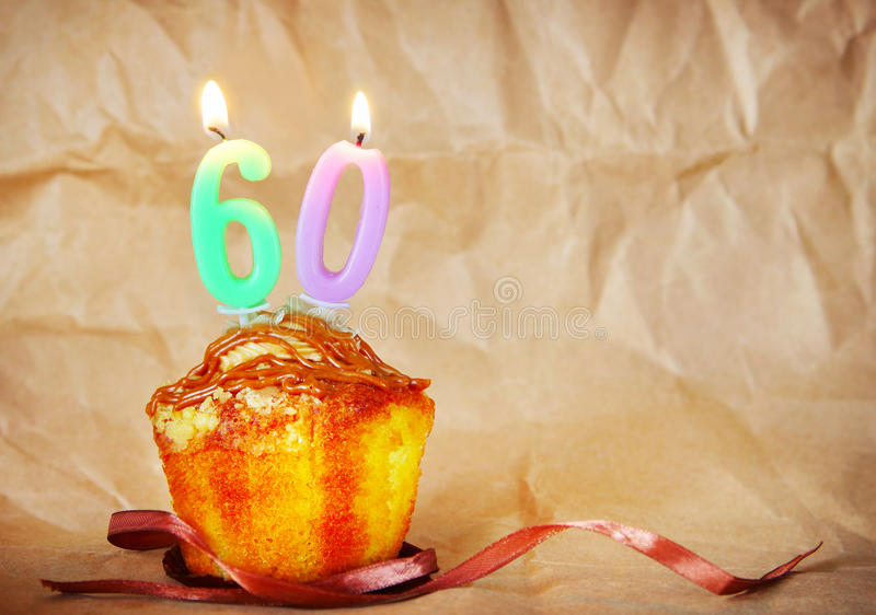 Birthday cake with burning candles as number sixty. On brown paper background royalty free stock image