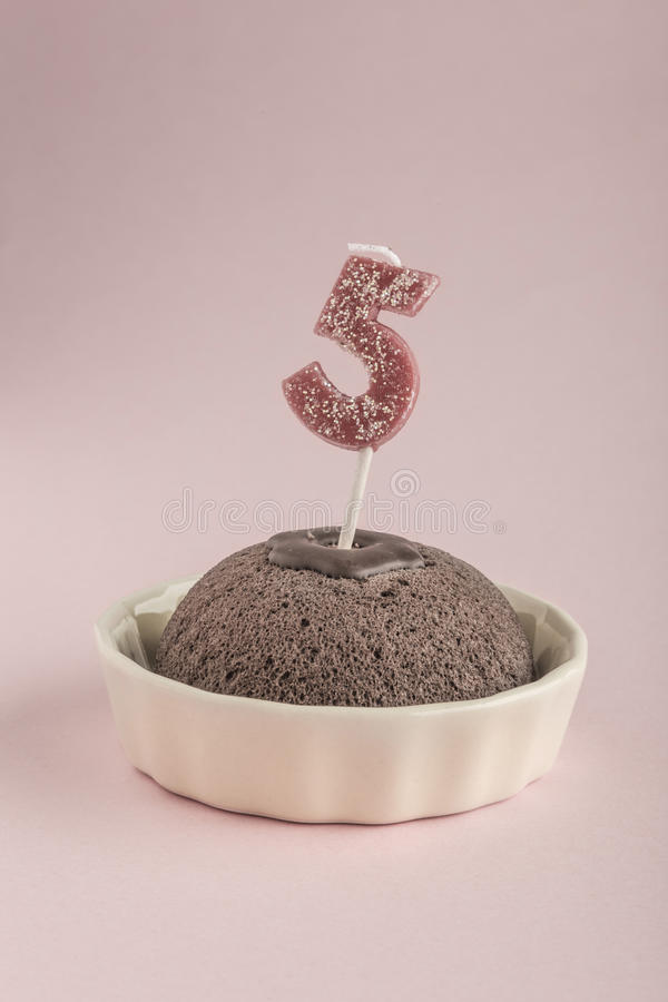 Birthday cake with candle age five. A small birthday cake with candle age five on pink royalty free stock images