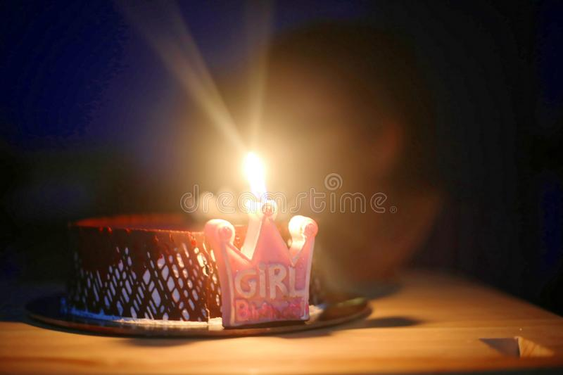 Birthday cake with candle. Lit in dark background stock images