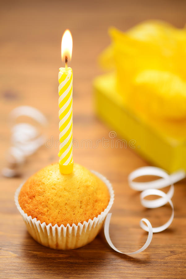 Birthday cake with candle. Birthday cake or muffin with a yellow candle on wooden table royalty free stock photos