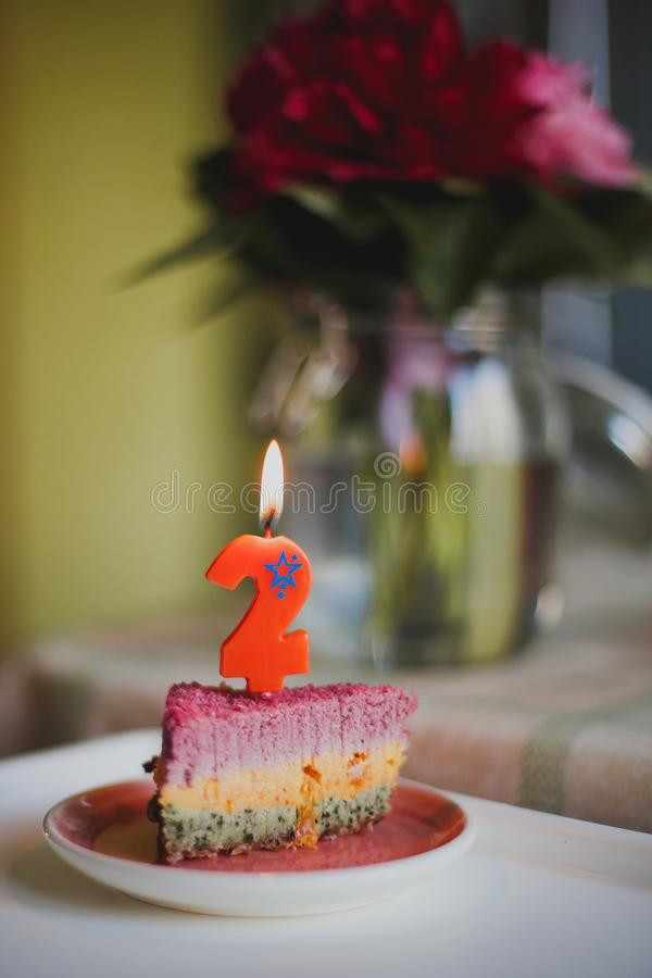 Birthday cake with a candle number two. A piece of delicious multi-colored birthday cake with a candle number two stock photography