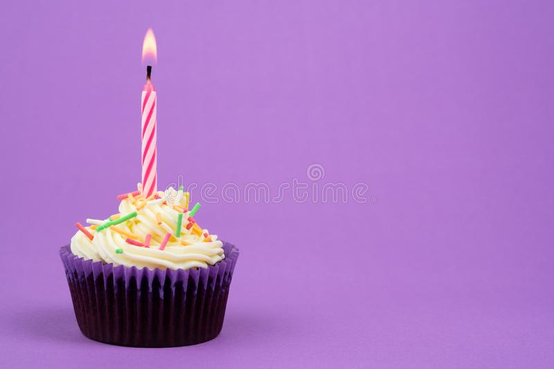 Birthday cake and candle. In purple stock photos