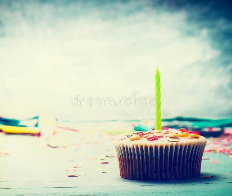 Birthday cake with candle on table at turquoise blue background. Front view royalty free stock image