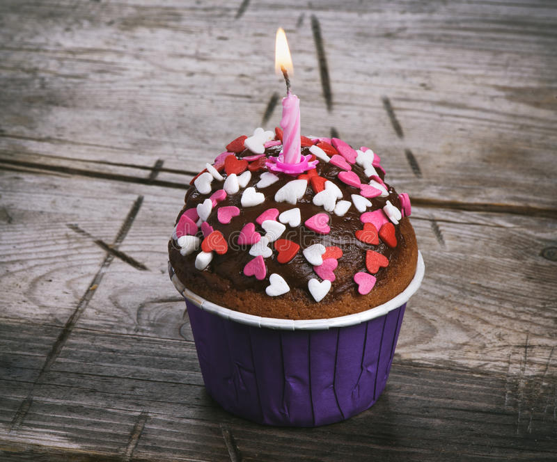 Birthday cake with candle. On wooden table stock image