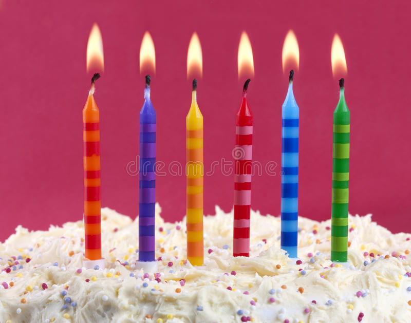 Birthday cake with candles. Birthday cake with 6 coloured candles on a red background stock images