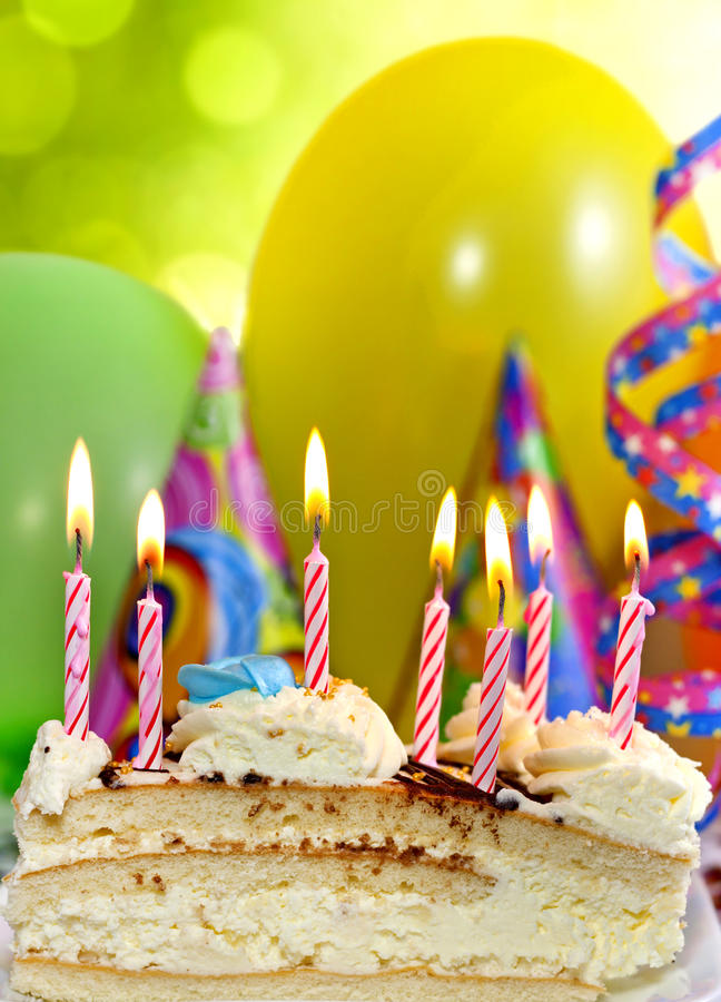 Birthday cake and candles. Happy birthday cake with candles and balloons against colorful bokeh background royalty free stock photos