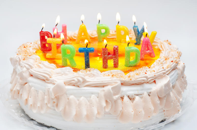 Birthday cake with candles. Appetizing birthday cake with the light colorful candles with text happy birthday royalty free stock image