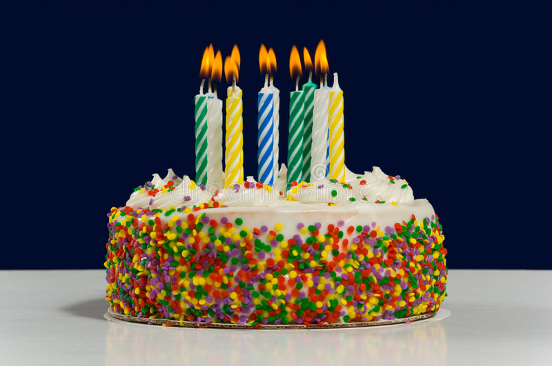 Birthday Cake and Candles. White birthday cake with candy sprinkles multi-colored candles on dark blue background stock image