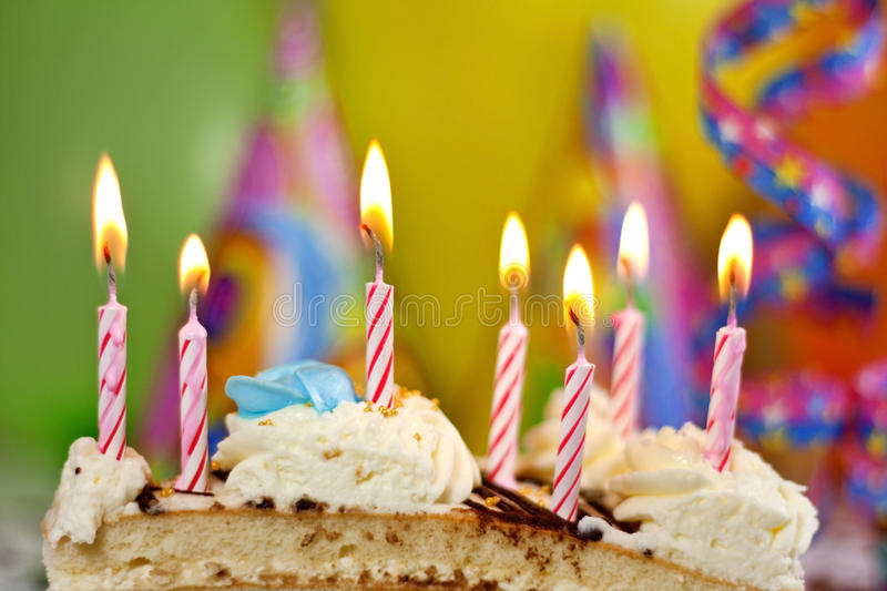 Birthday cake and candles background. Happy birthday cake with candles and balloons against colorful bokeh background royalty free stock photos