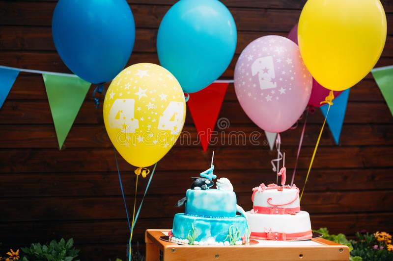 Birthday cake with candles and balloons in background. Birthday cake with candles and colorful balloons in background royalty free stock images