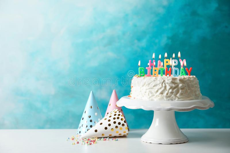 Birthday cake with candles. On table against color background royalty free stock photo