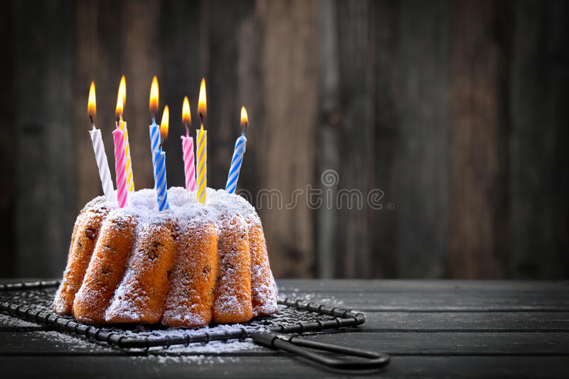 Birthday cake with candles. Delicious birthday cake with colorful candles on dark background royalty free stock photography