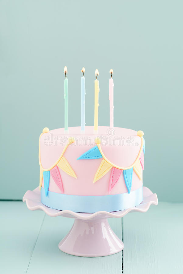 Birthday cake with candles. Fondant covered pastels coloured birthday cake with buntings and balloons stock photos