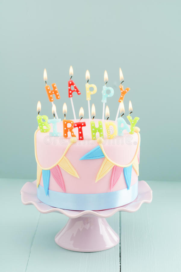 Birthday cake with candles. Fondant covered pastels coloured birthday cake with happy birthday candles stock image