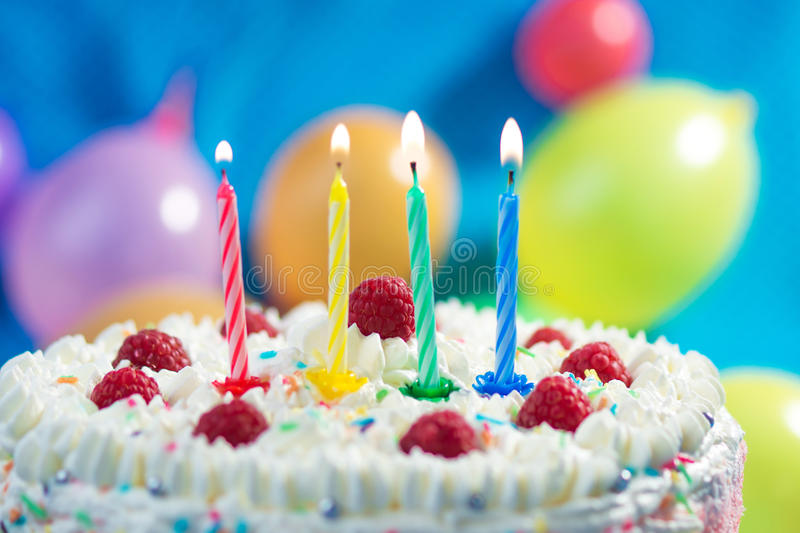 Birthday Cake. With candles lit up and ballons on the background royalty free stock photography