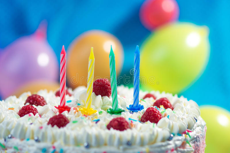 Birthday Cake. With candles lit up and ballons on the background stock images