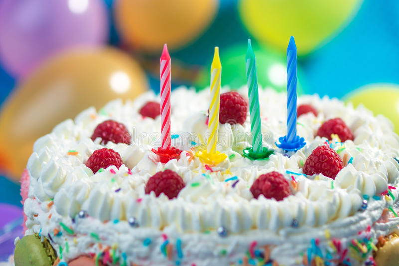 Birthday Cake. With candles lit up and ballons on the background stock photos