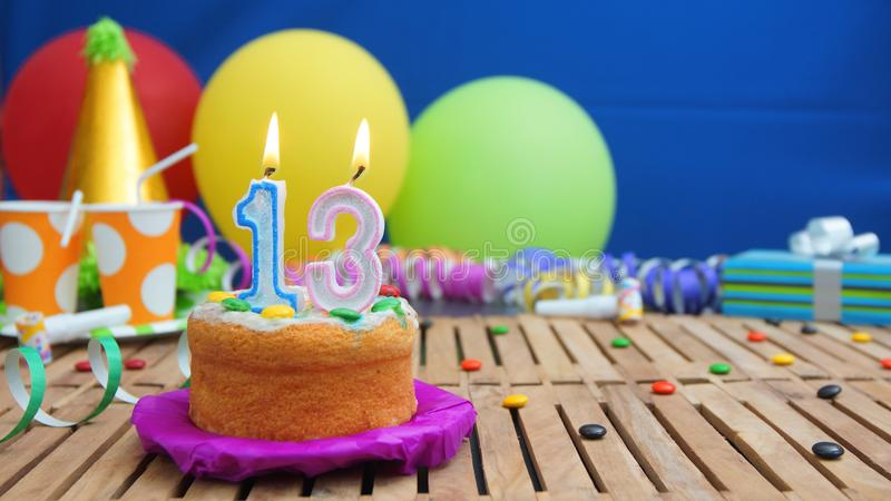Birthday 13 cake with candles on rustic wooden table with background of colorful balloons, gifts, plastic cups and candies. With blue wall in the background royalty free stock photos