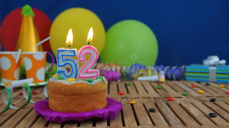 Birthday 52 cake with candles on rustic wooden table with background of colorful balloons, gifts, plastic cups and candies. With blue wall in the background stock photo