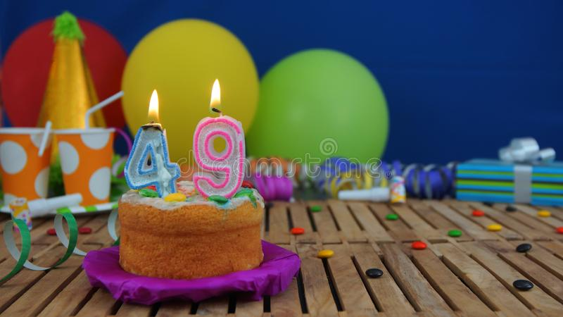 Birthday 49 cake with candles on rustic wooden table with background of colorful balloons, gifts, plastic cups and candies. With blue wall in the background royalty free stock image