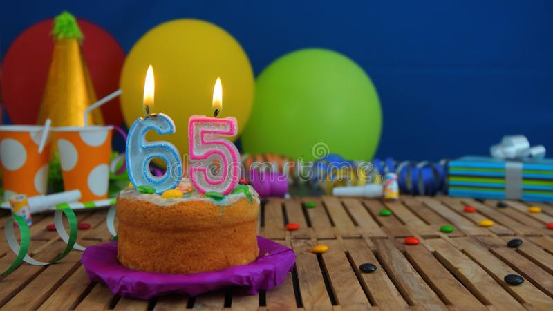 Birthday 65 cake with candles on rustic wooden table with background of colorful balloons, gifts, plastic cups and candies stock images