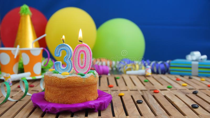 Birthday 30 cake with candles on rustic wooden table with background of colorful balloons, gifts, plastic cups and candies stock photography