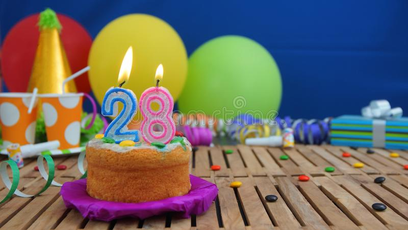 Birthday 28 cake with candles on rustic wooden table with background of colorful balloons, gifts, plastic cups and candies royalty free stock photos