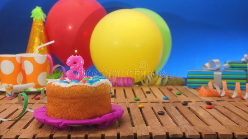 Birthday cake with candles on rustic wooden table with background of colorful balloons royalty free stock images