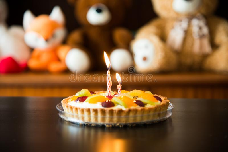 Birthday cake with candles, soft toys as background stock photography
