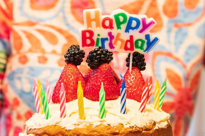 Birthday cake with candles, strawberries, blackberries and a sign saying Happy Birthday royalty free stock images