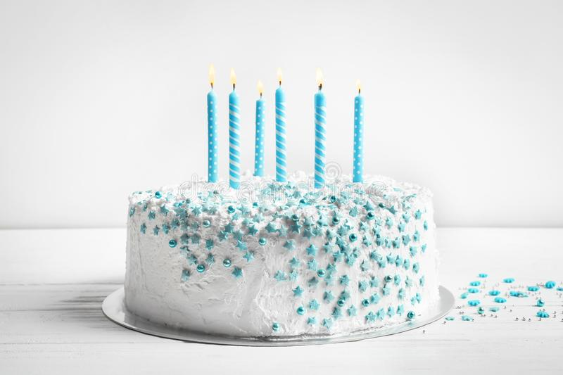 Birthday cake with candles on table against wall. Birthday cake with candles on table against light wall royalty free stock image