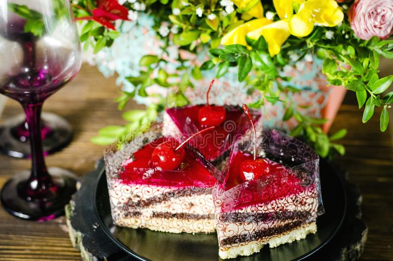 Cake with cherry. Birthday cake with cherry on a background of flowers stock images