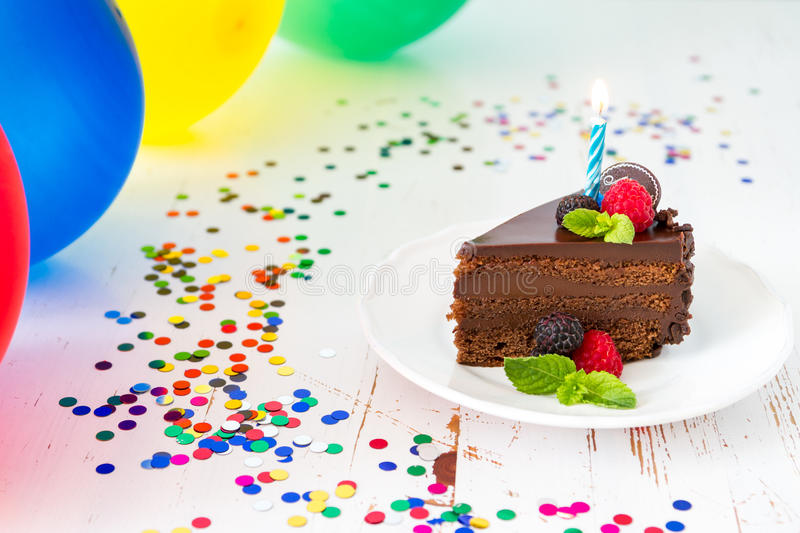 Birthday cake. Birthday chocolate cake with candle, light blue background, bokeh stock image
