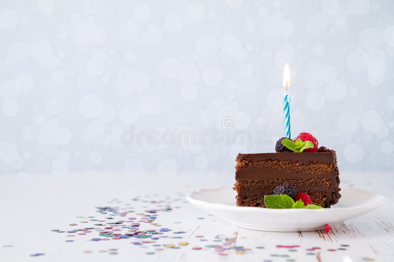 Birthday cake. Birthday chocolate cake with candle, light blue background, bokeh royalty free stock photos