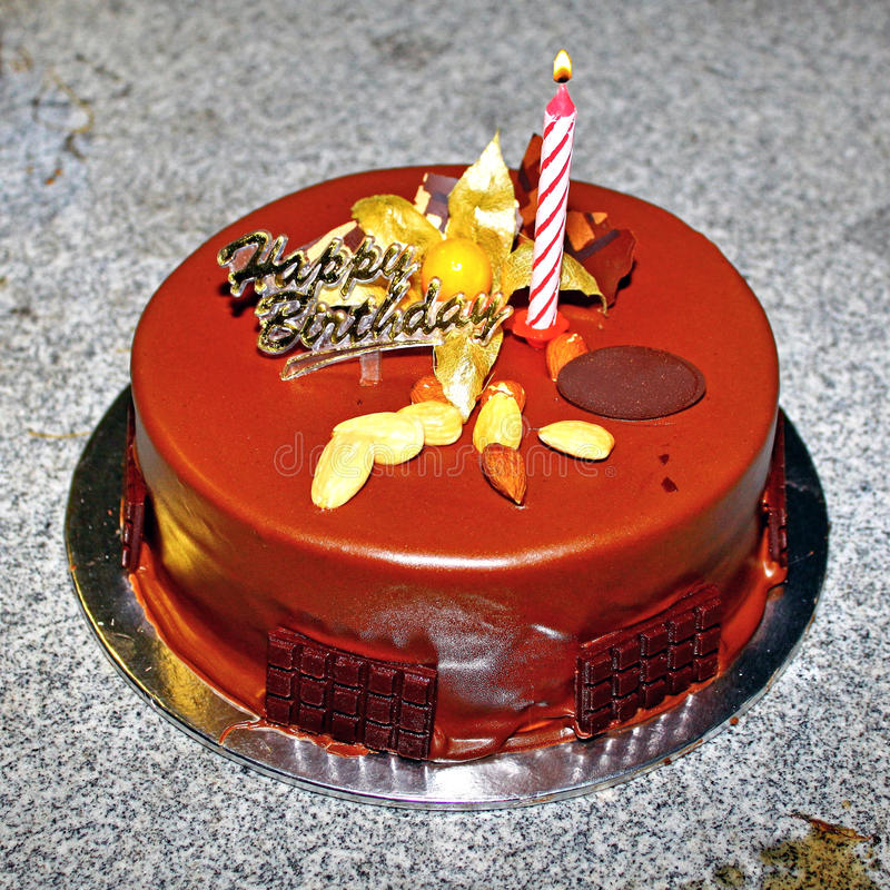Birthday cake. Chocolate birthday cake with some nuts and a single candle. Image photographed on 12 February 2010 stock photo