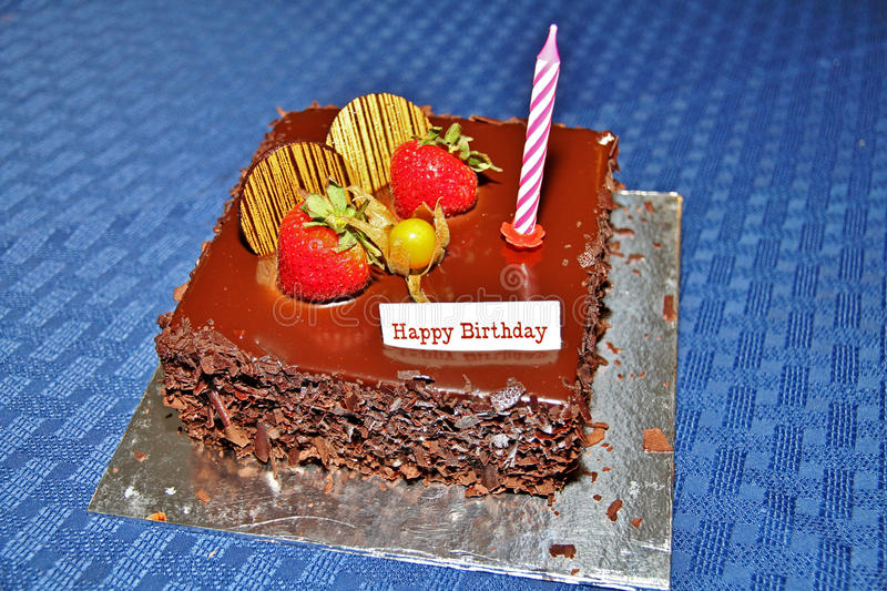 Birthday cake. Chocolate birthday cake with strawberries and a single candle.nnImage photographed on 12 February 2010 royalty free stock photo