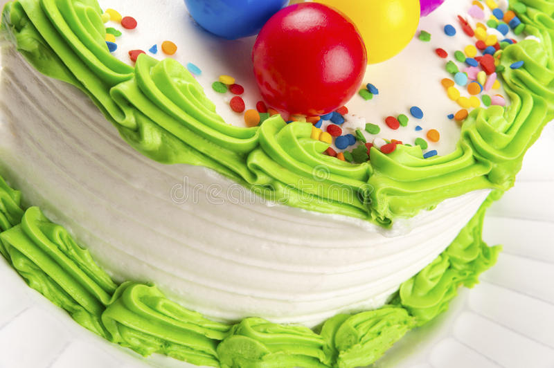 Birthday Cake Closeup. Closeup of white birthday cake green icing trim and multi-color sprinkles and colored balls royalty free stock image