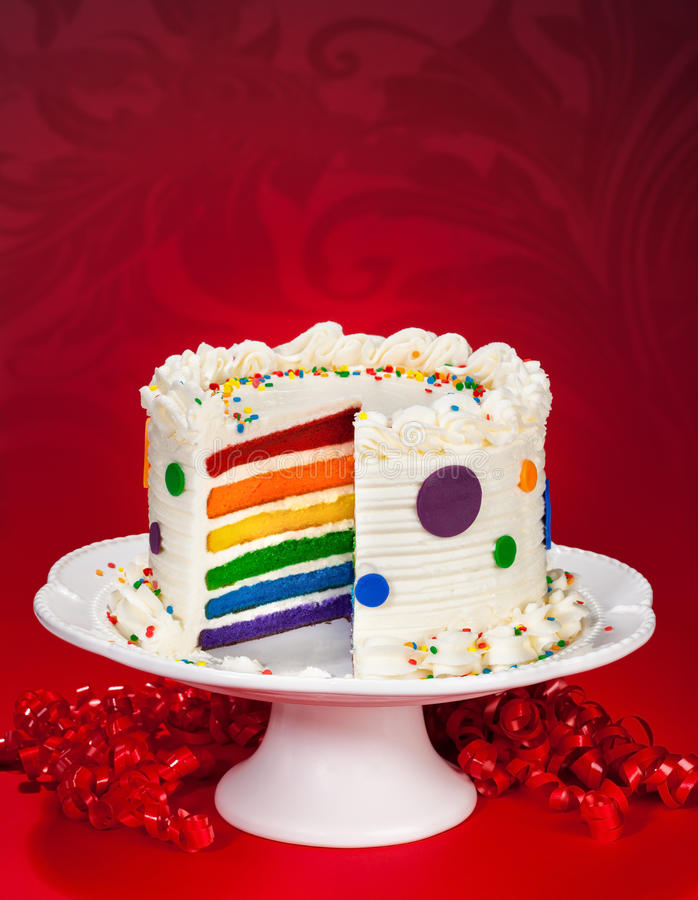 Birthday Cake. Colorful layered birthday cake with white butter cream frosting and sprinkles on a nice red background royalty free stock photos