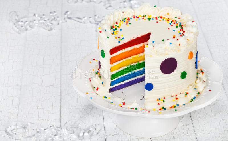 Birthday Cake. Colorful rainbow layered birthday cake decorated with polka dots, sprinkles and buttercream icing stock photos