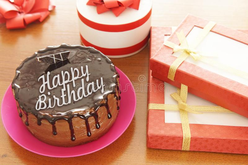 Birthday cake with a congratulatory text on above and a lot of gifts stock photo