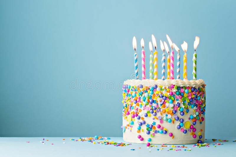 Birthday cake decorated with colorful sprinkles and ten candles. Colorful birthday cake with sprinkles and ten candles on a blue background with copyspace stock photos